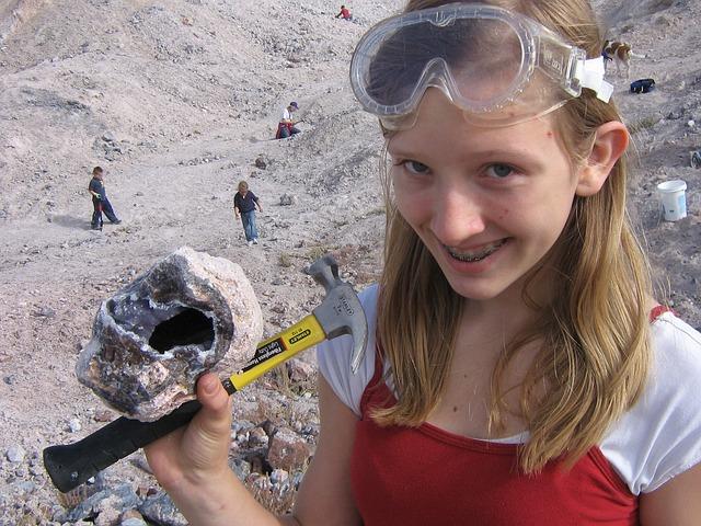 smějící se dívka do kamery držící kladívko